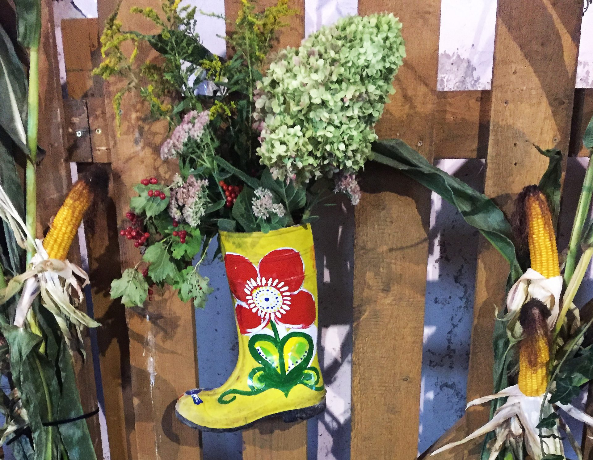 bemalter Gummistiefel hängt am Gartentor